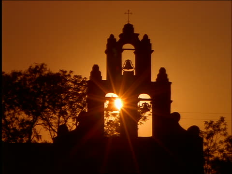stockvideo's en b-roll-footage met time lapse sunset behind silhoutte of bells of mission san juan / san antonio, texas - kleine groep dingen