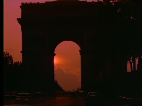 vidéos et rushes de time lapse sunset + clouds behind silhouette of arc de triomphe - arc élément architectural