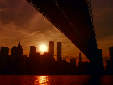 vídeos de stock e filmes b-roll de time lapse sunset + clouds over silhouette of lower manhattan seen from under brooklyn bridge - world trade center manhattan