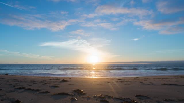 vídeos de stock, filmes e b-roll de time lapse: sunset on horizon of ocean and beach fading into night - dia