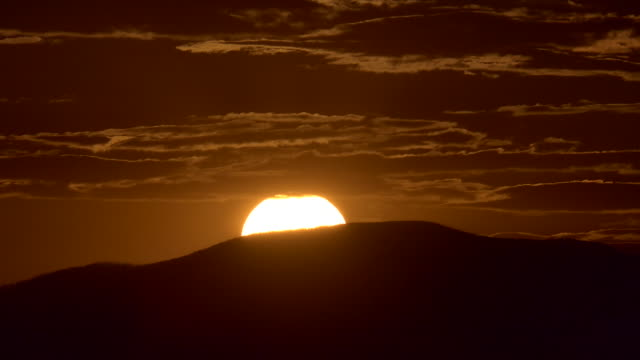 vídeos de stock, filmes e b-roll de time lapse sunset over a mountain with colorful orange clouds - sudoeste dos estados unidos