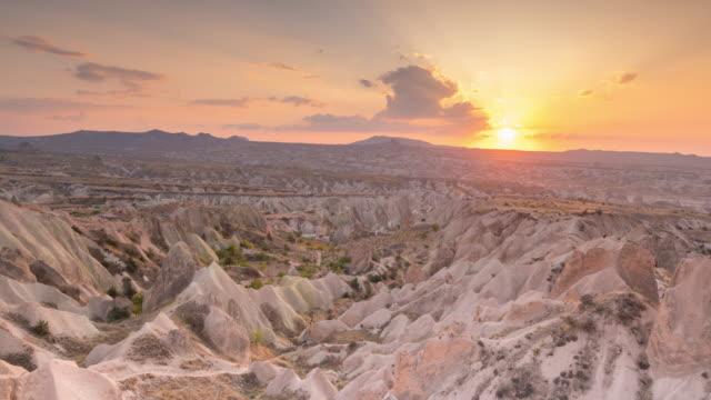 vidéos et rushes de time lapse : sunset panoramic paysage rocheux anciennes maisons troglodytes à goreme, cappadoce, turquie - vallée
