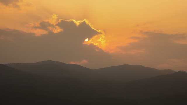 4k t/l time lapse sunset passing cloud behind hills - mack2happy stock videos and b-roll footage