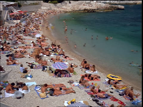 time lapse swimmers + sunbathers on crowded beach in cassis / southern france - region provence alpes côte d'azur stock-videos und b-roll-filmmaterial