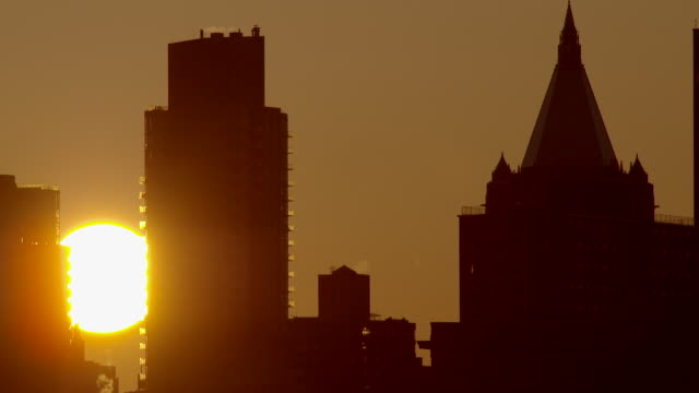 Time lapse telephoto shot of the sun rising between skyscrapers in Manhattan early morning