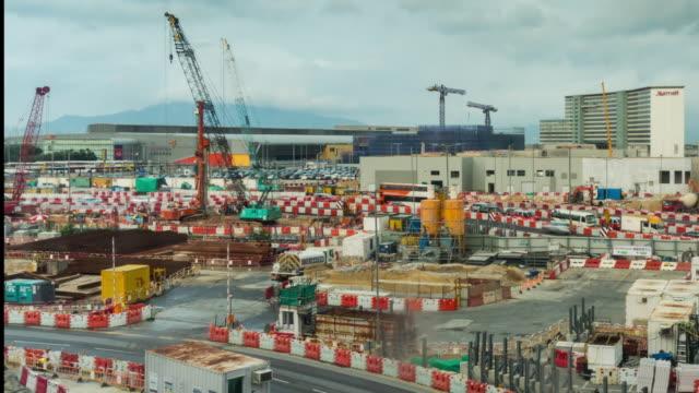 vidéos et rushes de time lapse: le chantier de construction à l'aéroport international de hong kong avec un fond de ciel nuageux en mouvement. - hlm
