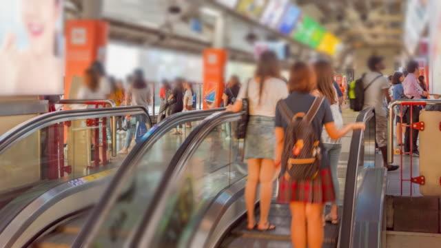 時間の経過: 群衆の中の乗客と鉄道駅のエスカレーター - 高架電車点の映像素材/bロール