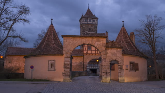 time lapse. the famous city gate called röder tor and röder tower with traffic illuminated at dusk. röder tor, rothenburg ob der tauber, franconia, bavaria, germany. - mittelalterlich stock-videos und b-roll-filmmaterial
