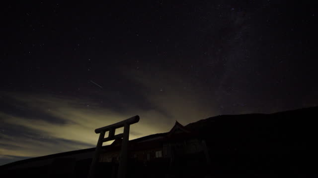 vidéos et rushes de time lapse: the starry night sky with the silhouette of the torii gate on hakusan - sanctuaire