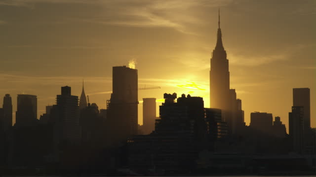Time Lapse.  The sun is rising behind The Empire States Building early morning.  The sky is a fiery yellow and orange behind the buildings.  Construction Elevators go up and down as well as cranes travel around..
