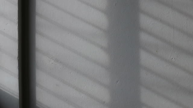 vídeos de stock e filmes b-roll de time lapse: the sunlight background shines through the window onto a white concrete wall. - parede