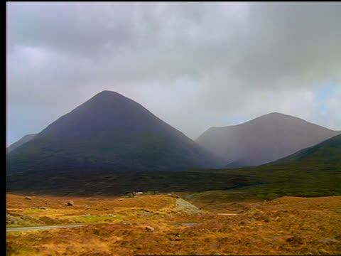 time lapse thick clouds + fog passing over mountains + car on country road / isle of skye, scotland - ヘブリディーズ点の映像素材/bロール