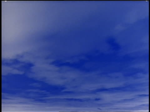 stockvideo's en b-roll-footage met time lapse thin cloud cover moving in blue sky / changes to negative image of blue clouds in white sky - cross processen