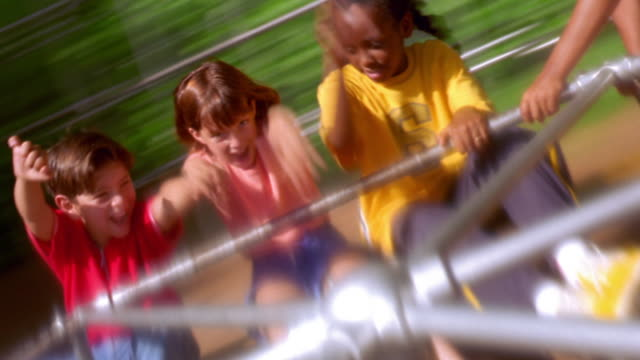 canted time lapse three children smiling + raising arms on merry-go-round with girl pushing / florida - playground stock videos & royalty-free footage