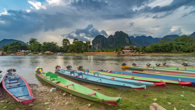 4K tidsfördröjning: turist- och lång svans båtar och solnedgång på låten river, Vang Vieng, Laos.