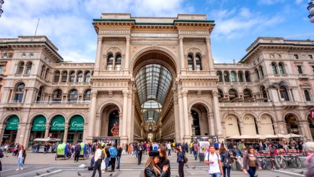 4k time lapse : tourist crowd traveling at milan shopping gallery vittorio emanuele facade front  , italy - tourist video stock e b–roll