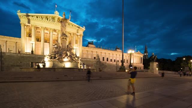 zeitraffer, touristische aufwachen am parlamentsgebäude in der abenddämmerung - austria flag stock-videos und b-roll-filmmaterial