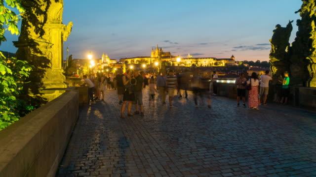 vídeos de stock, filmes e b-roll de lapso de tempo, turista andando na ponte charles, ao entardecer, praga - ponte carlos