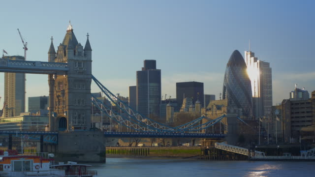 Time lapse Tower Bridge with traffic and boats on River Thames at sunset in London.