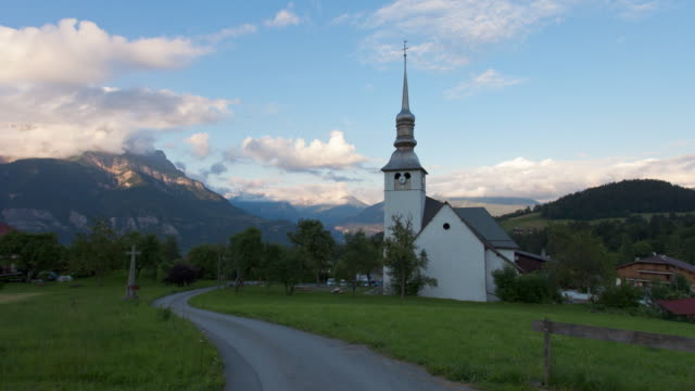 Time Lapse tracking shot in front of a baroque church with Mont Blanc chain in the back