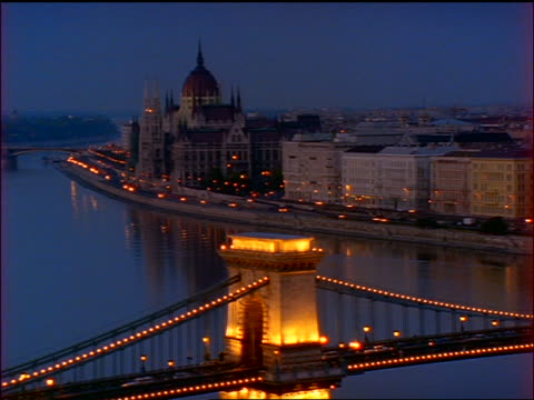 time lapse traffic at dusk of chain bridge over danube river / parliament building in background / budapest - chain bridge suspension bridge stock-videos und b-roll-filmmaterial