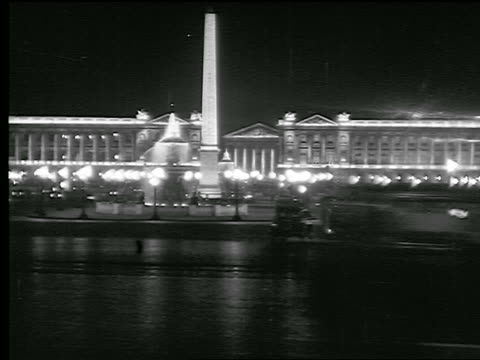 B/W 1936 time lapse traffic in Place de la Concorde with Obelisk, fountain at night / Hotel Crillon in background