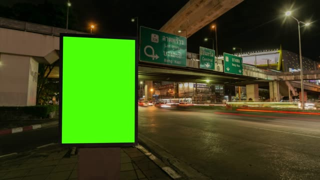 time lapse, traffic long exposure on road with billboard green screen use for advertising street signs in city. - placard stock videos & royalty-free footage