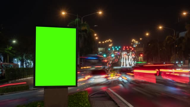 time lapse, traffic long exposure on road with billboard green screen use for advertising street signs in city. - tabellone video stock e b–roll