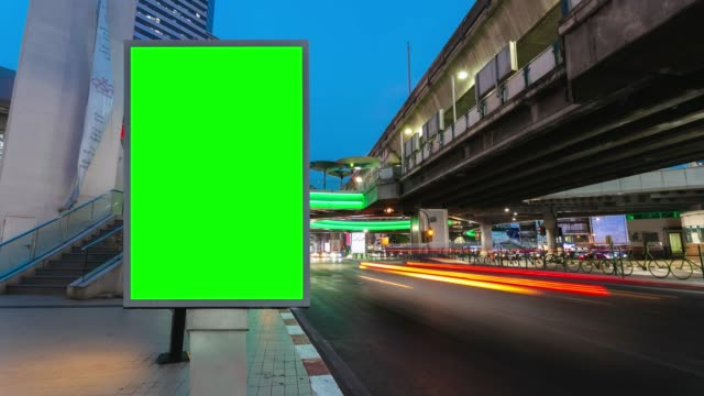 vídeos de stock e filmes b-roll de time lapse, traffic long exposure on road with billboard green screen use for advertising street signs in city. - long exposure