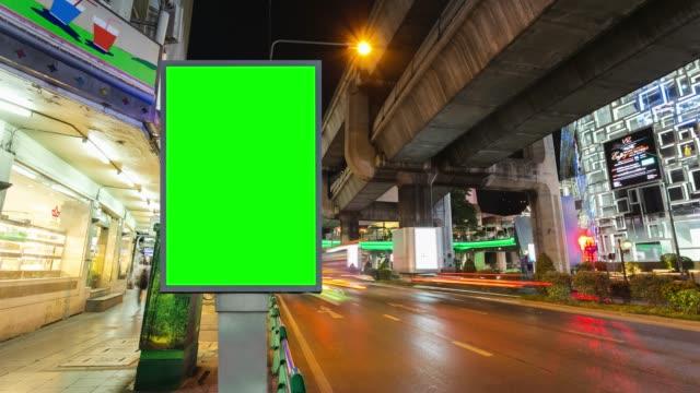 vídeos de stock, filmes e b-roll de lapso de tempo, longa exposição de tráfego na estrada com o uso de tela verde da billboard para publicidade de placas de rua na cidade. - long exposure