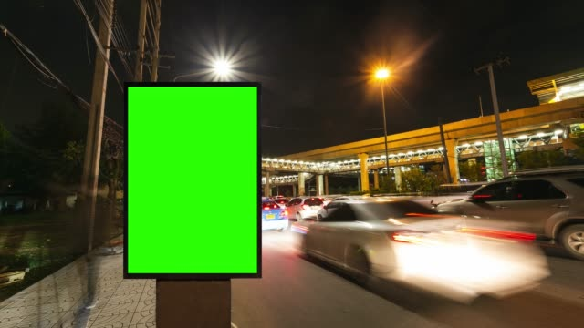 time lapse, traffic long exposure on road with billboard green screen use for advertising street signs in city. - poster stock videos & royalty-free footage