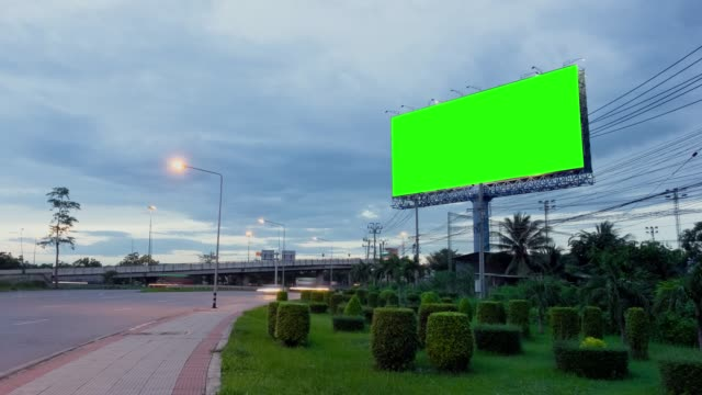 vídeos de stock e filmes b-roll de time lapse, traffic night long exposure on road with billboard green screen use for advertising. - advertisement