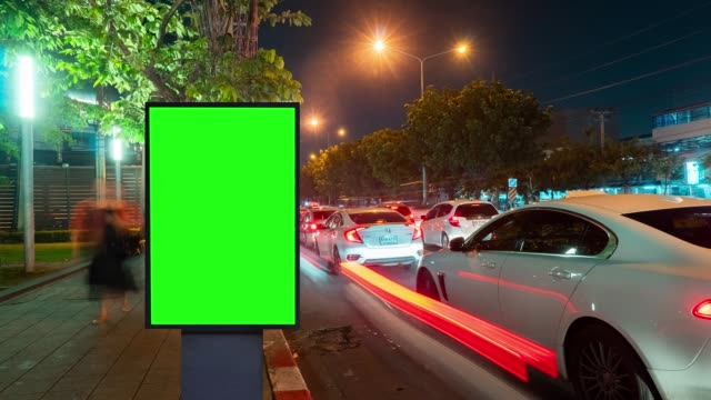 vídeos de stock e filmes b-roll de time lapse, traffic night long exposure on road with billboard green screen use for advertising. - billboard