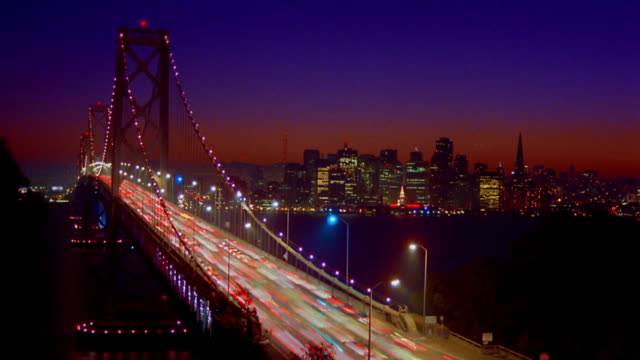 time lapse traffic on bay bridge at dusk / cityscape in background / san francisco, california - san francisco oakland bay bridge stock videos and b-roll footage