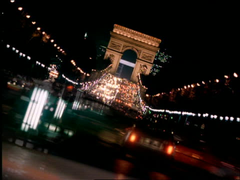 canted time lapse traffic on champs elysees with arc de triomphe in background at night / paris - french culture stock videos & royalty-free footage