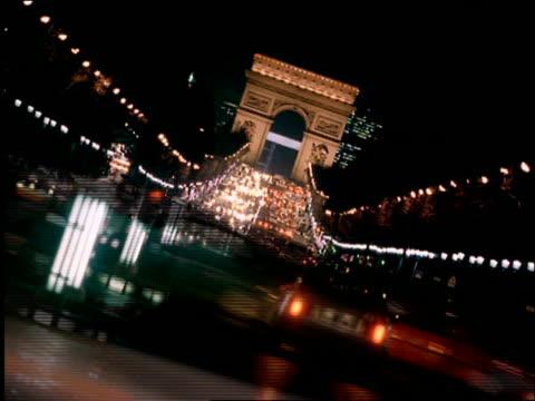 vidéos et rushes de canted time lapse traffic on champs elysees with arc de triomphe in background at night / paris - arc élément architectural