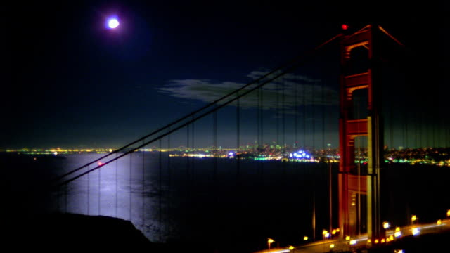 time lapse traffic on golden gate bridge at night / boats, planes and moon rising over san francisco bay background - san francisco bay area stock videos & royalty-free footage