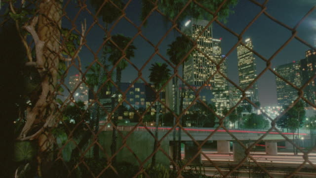 pan time lapse traffic on highway with skyscrapers in background at night / chain link fence in foreground / los angeles, ca - wire mesh fence stock videos & royalty-free footage