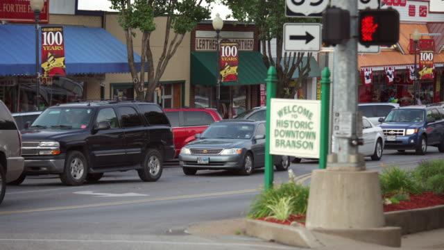 "time lapse traffic on main street and ""welcome to historic downtown branson"" sign - butiksskylt bildbanksvideor och videomaterial från bakom kulisserna"