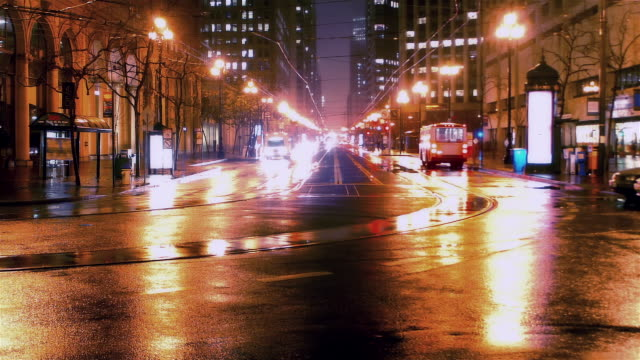 time lapse traffic on rainy mission street at night / san francisco, california - trolley bus stock videos & royalty-free footage
