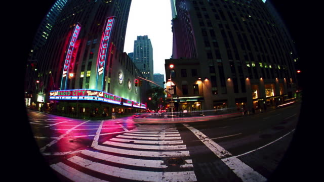 pan time lapse traffic on sixth avenue in front of radio city music hall at twilight / nyc - radio city music hall stock videos & royalty-free footage