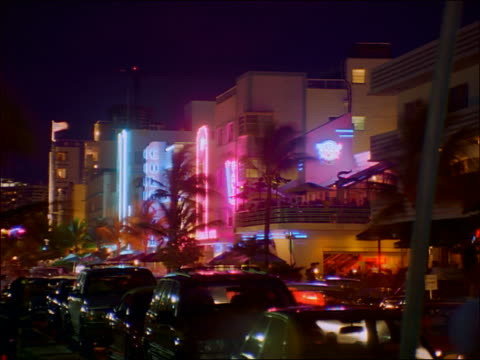 time lapse traffic + people in front of art deco buildings on city street at night / miami beach, miami - アールデコ点の映像素材/bロール