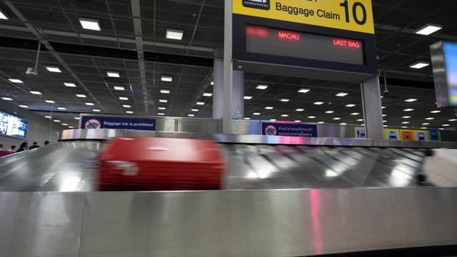 4kタイムラプス:空港で手荷物ベルトの上を移動するトラベラーバッグ - ベルト点の映像素材/bロール