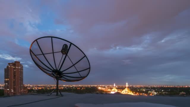 tidsfördröjning skymning till natt av moln flyttar över parabolantenn antenner - radio och tv utsändning bildbanksvideor och videomaterial från bakom kulisserna
