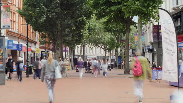 4k time lapse unidentifiable people busy shoppers on shopping high street background - ommuters on city centre high street on sunny day as retail small and medium business trade starts to boom - traffic time lapse stock videos & royalty-free footage