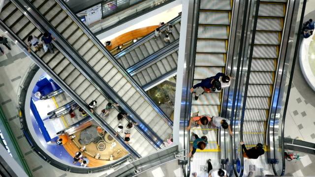 Time-lapse, niet-geïdentificeerde mensen op een roltrap in een winkelcentrum