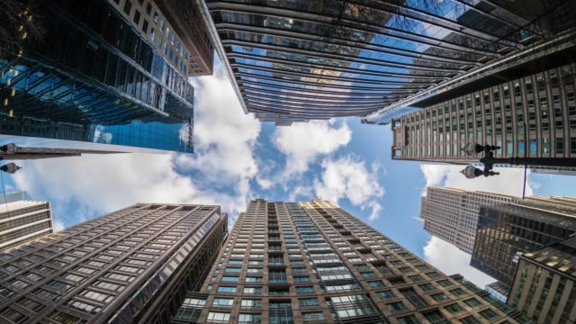 vídeos de stock e filmes b-roll de 4k time lapse uprisen angle of downtown chicago skyscraper with reflection of clouds among high buildings in fisheye angle, illinois, united states, business and perspective concept - arranha céu