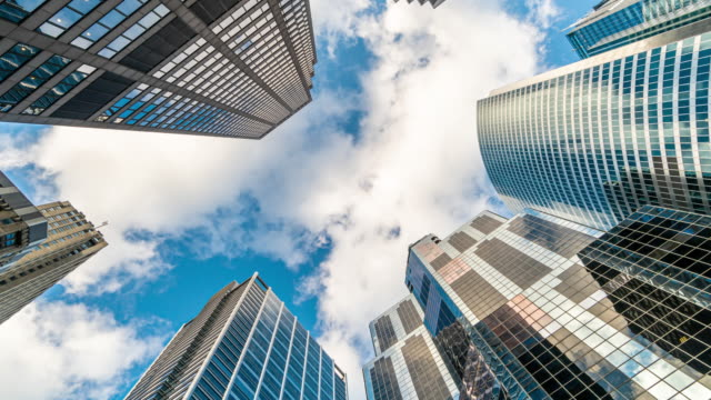 4k time lapse uprisen angle of downtown chicago skyscraper with reflection of clouds among high buildings, illinois, united states, business and perspective concept - edificio adibito a uffici video stock e b–roll