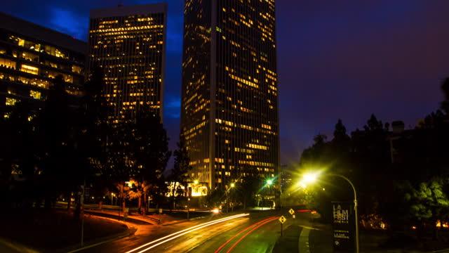 time lapse upward shot of vehicles moving on road in illuminated city at dusk - century city, california - century city stock videos & royalty-free footage