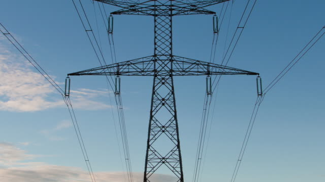 Time lapse vertical pan of electrical pylon at sunset